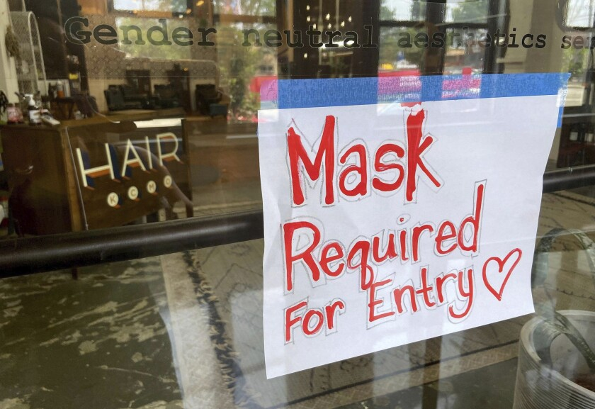This July 28, 2021 file photo shows a sign on the door of a hair salon.