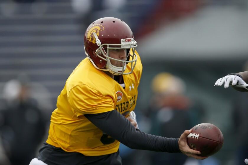 Former USC quarterback Cody Kessler hands off during Senior Bowl practice in Mobile, Ala.