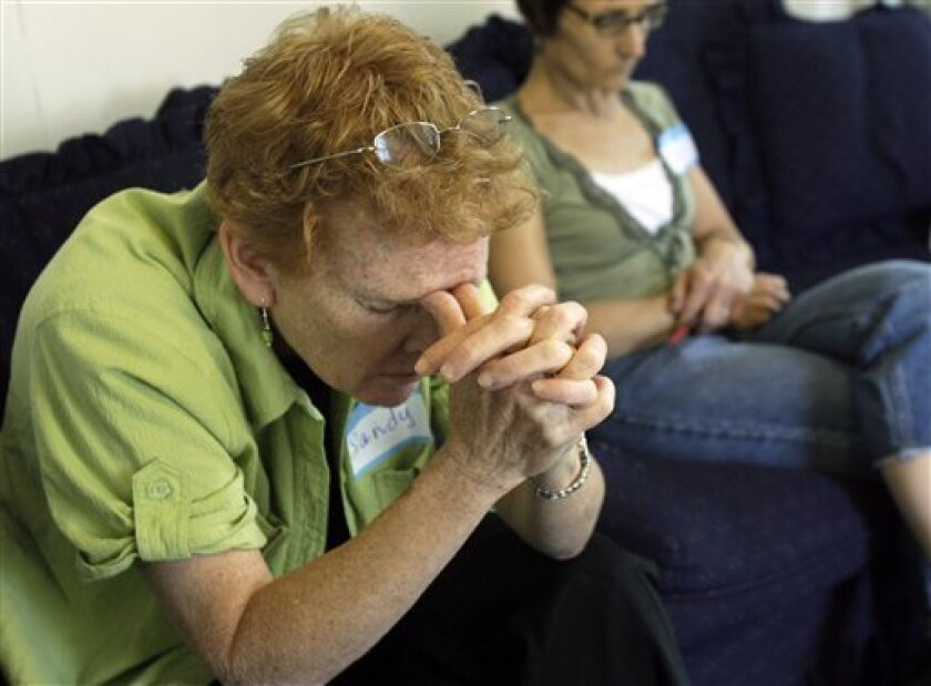 This June 4, 2009 photo shows Sandra Friedrich, left, of Wenham, Mass. and Debbie Gonzalez of Saugus, Mass. praying during an unemployed support group meeting in Beverly, Mass. The group is one of several church-related unemployment support groups that have formed around the country as the jobless rate reaches heights not seen for decades. (AP Photo/Elise Amendola)