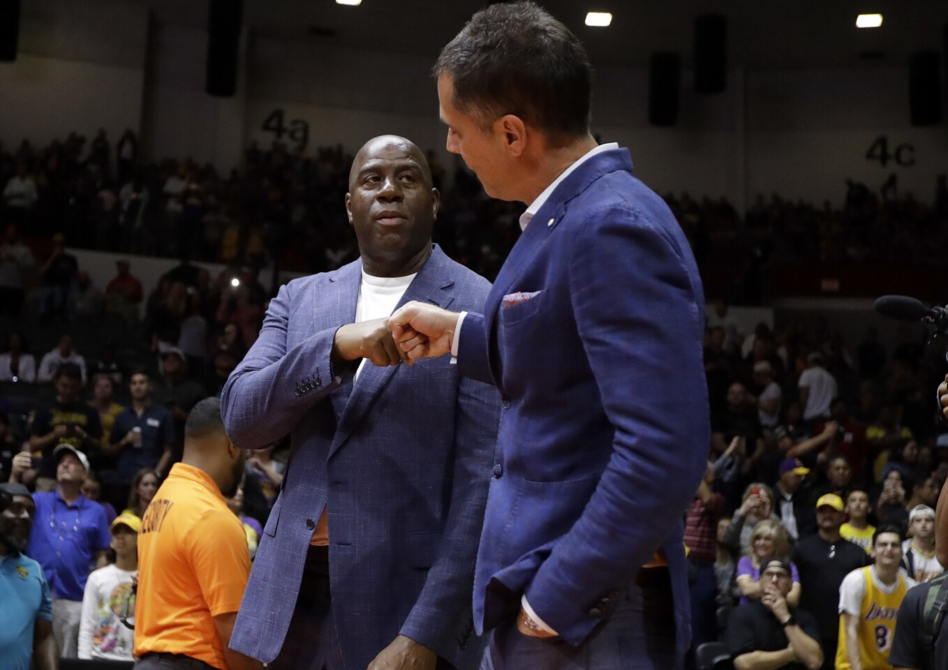 Los Angeles Lakers president of basketball operations Earvin Magic Johnson, left, bumps fists with general manager Rob Pelinka before an NBA preseason basketball game against the Denver Nuggets Sunday, Sept. 30, 2018, in San Diego.