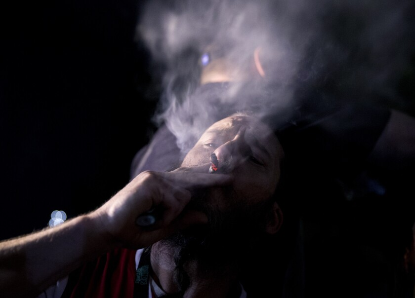 A person smokes at a celebration for the legalization of recreational marijuana on July 1 in Portland, Ore.