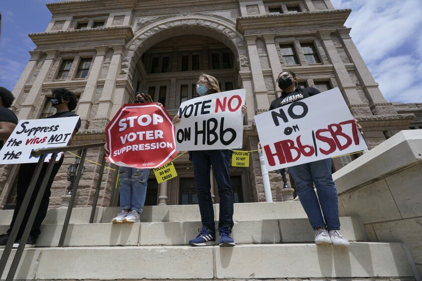 """People hold up signs reading """"Stop voter suppression"""" and """"Vote no on HB6."""""""