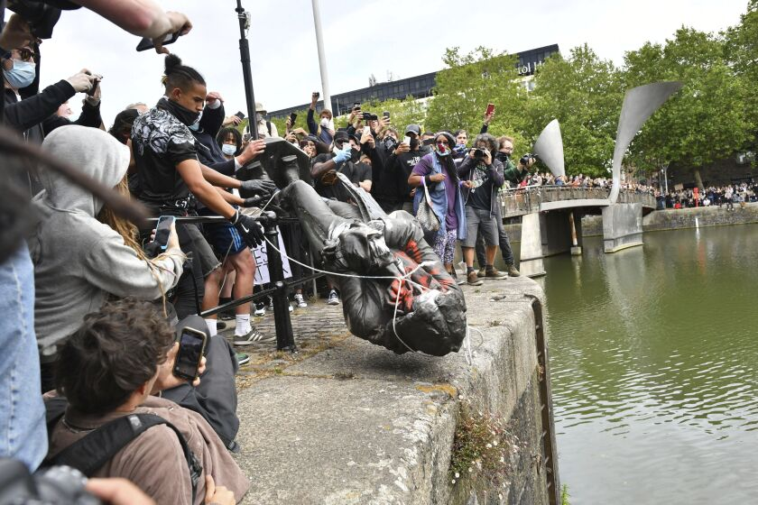 Protesters throw a toppled, tied-up statue of slave trader Edward Colston into the harbor in Bristol, England as crowd cheers