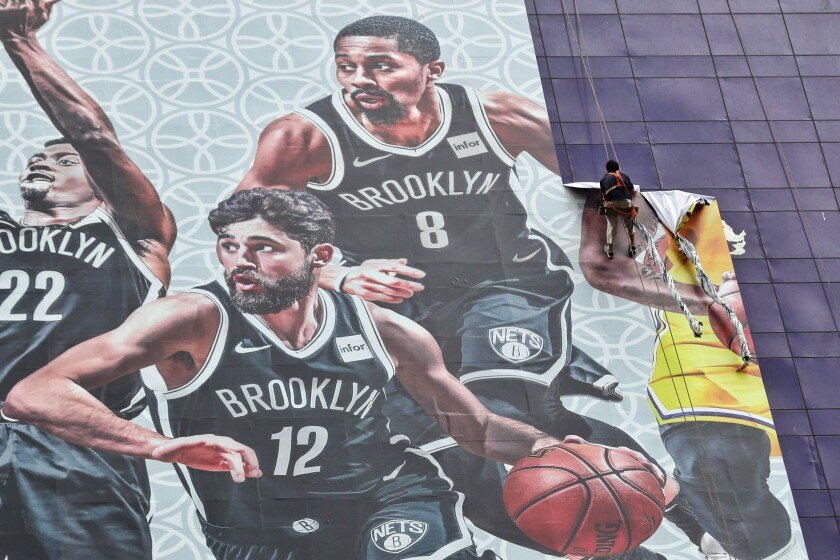 Worker in Shanghai removes a banner advertising Lakers-Nets game