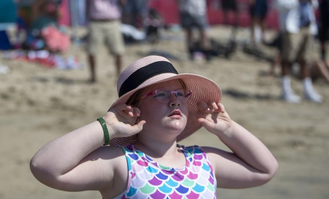 Emma Lewis, 8, of Las Vegas plugs her ears as a Navy EA-18 Growler flies over