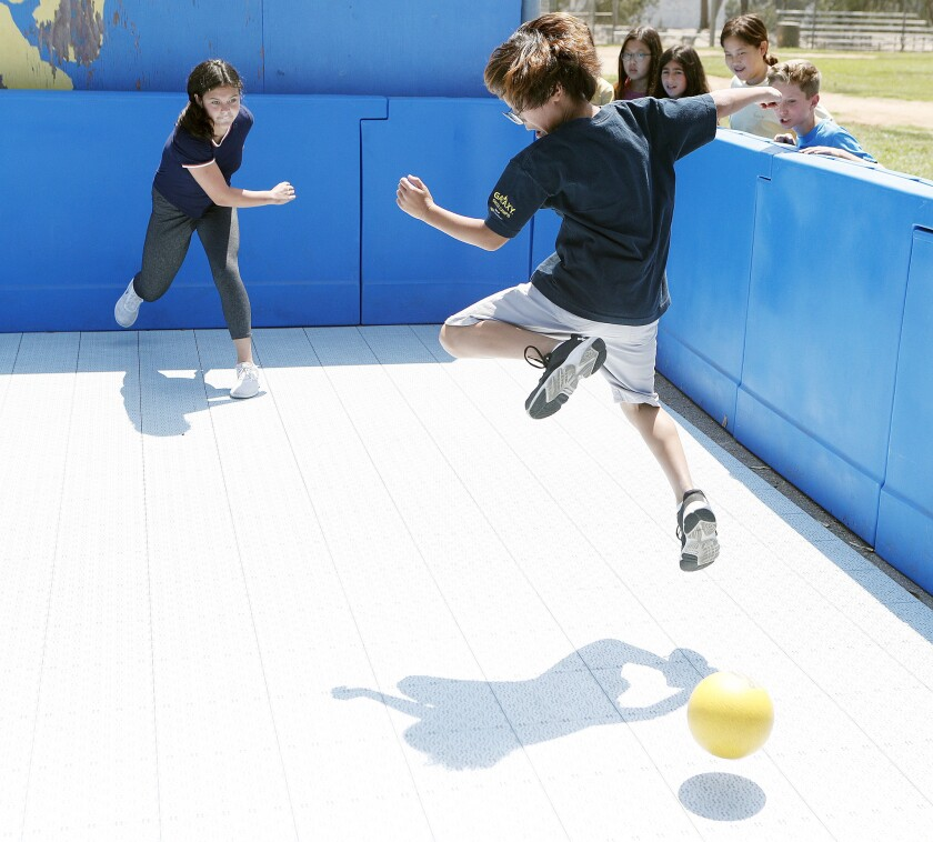 Cody Mora, 12, hits the ball making opponent Keoney Lee, 11, jump to avoid being hit in a newly installed gaga pit for students to play gaga ball at La Cañada Elementary School on Tuesday, August 21, 2018. The game is a lot like dodge ball, but the ball is hit with a hand and is live until an opponent hits the ball with their hand. If the ball hits you before you can hit it, your out.