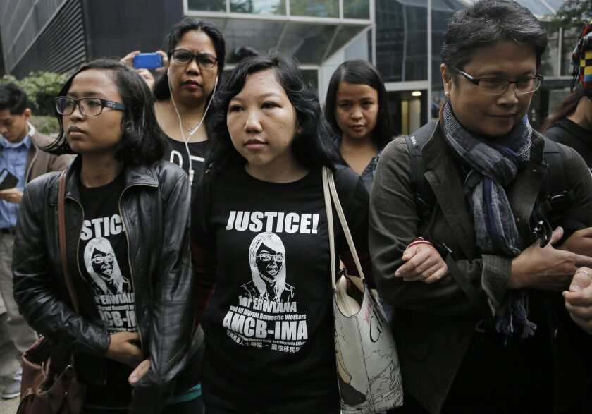 Indonesian maid Erwiana Sulistyaningsih, center, is accompanied by supporters as she arrives at a court in Hong Kong, Friday, Feb. 27, 2015. A Hong Kong court sentenced a mother of two to six years in prison on Friday for abusing her Indonesian maid in a case that triggered outrage over its brutality. Law Wan-tung was found guilty earlier this month on 18 charges, including assault, grievous bodily harm, criminal intimidation and failure to pay wages or give time off work to Sulistyaningsih. (AP Photo/Vincent Yu)