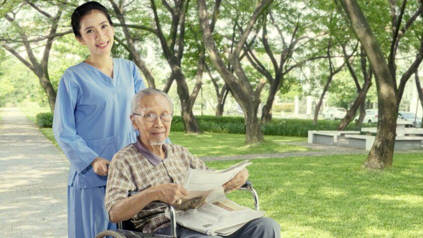 Cheerful nurse with elderly man in the park