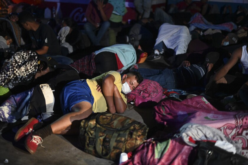 A man rests his head on a backpack to sleep among a crowd of migrants