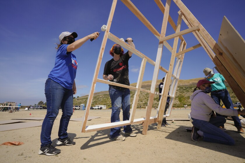 Volunteers paint the roof rafters and sheets of plywood that will be used in building pre-fabricated homes