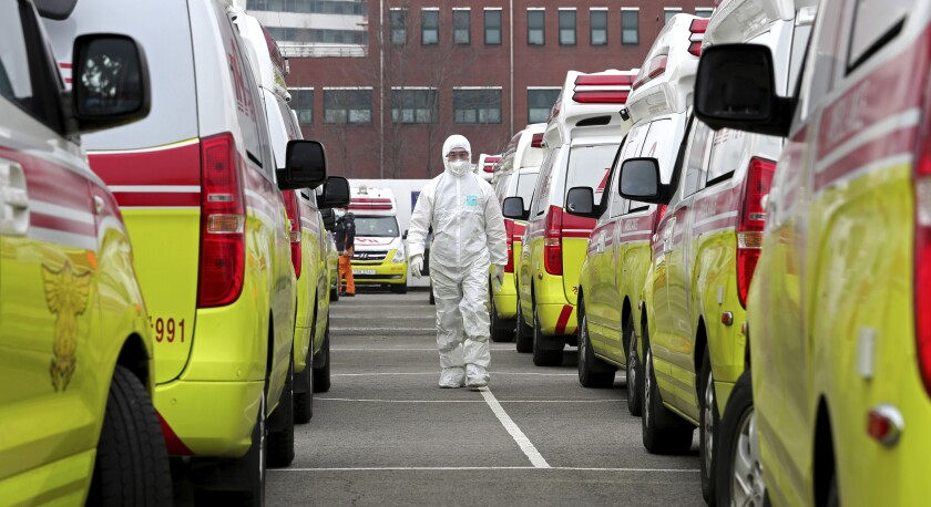 A health worker wearing a protective suit walks between the ambulances to transport patients in Daegu, South Korea, Sunday, March 1, 2020. The coronavirus has claimed its first victim in the United States as the number of cases shot up in Iran, Italy and South Korea and the spreading outbreak shook the global economy.(Ryu Young-seok/Yonhap via AP)