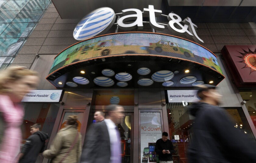 People pass an AT&T store in New York. AT&T may combine media operations that include CNN, HBO, TNT and TBS with Discovery