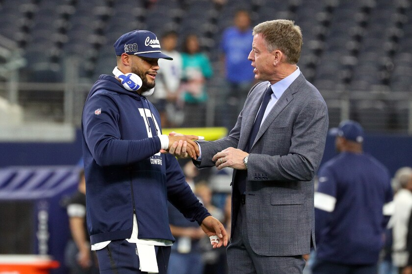 Dallas Cowboys quarterback Dak Prescott shakes hands with Fox Sports NFL analyst and former Cowboys quarterback Troy Aikman.