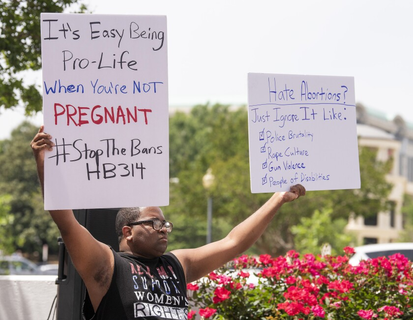 Travis Jackson holds signs during a protest against HB314, the abortion ban bill, at the Alabama Sta