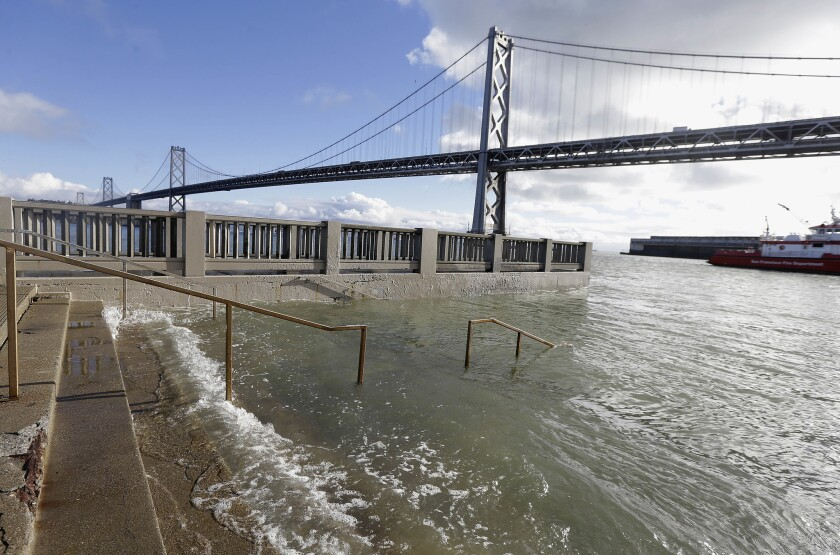 High tide floods a staircase along the Embarcadero in San Francisco