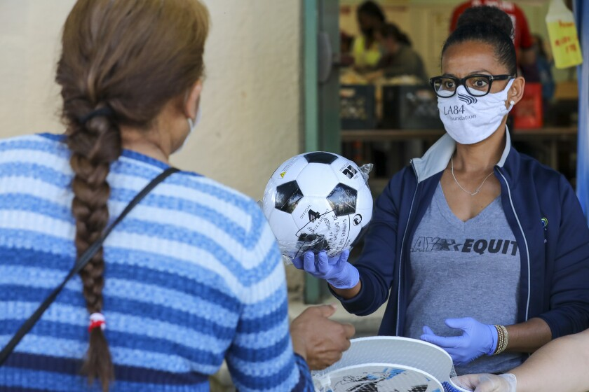 Renata Simril, of LA84 Foundation, distributes sports goods to under-served kids, at LAUSD Grab and Go meal center at Thomas Alva Edison School on Wednesday in Los Angeles.