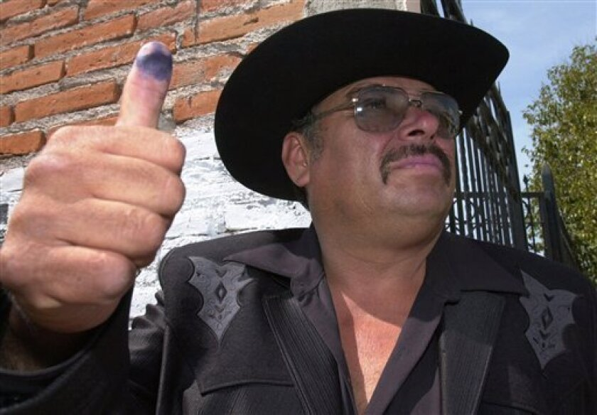 "Andres Bermudez, candidate for mayor and U.S. resident, shows his thumb after casting his vote in Jerez, Mexico, in this Sunday, July 1, 2001 file photo. Bermudez, also known as "" The Tomate King"", nickname he earned after inventing the tomato-planting machine that turned him into millionaire, who made history by becoming the first migrant living in the United States to win a Mexican mayorship. Bermudez died of cancer at the age of 58, Thursday, Feb. 5, 2009.(AP Photo/Gregory Bull)"