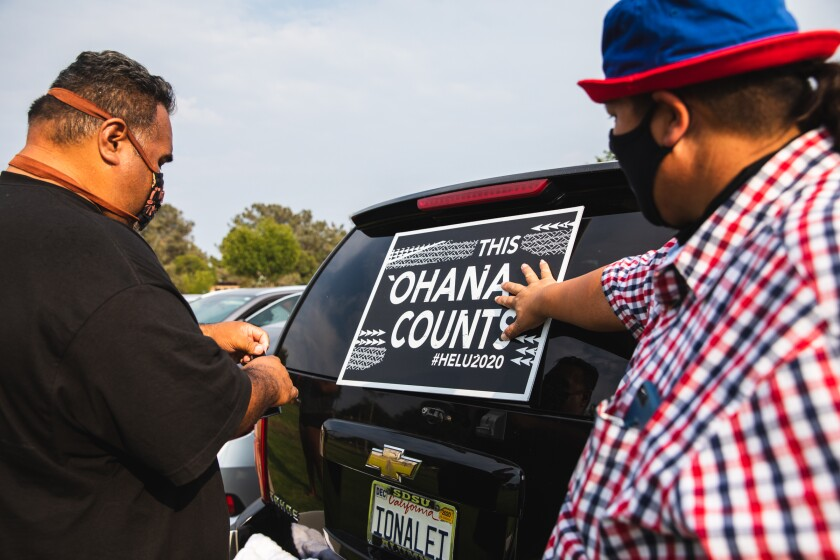 Tana Lepule and Eddie Paje put posters on an SUV to encourage participation in the census.