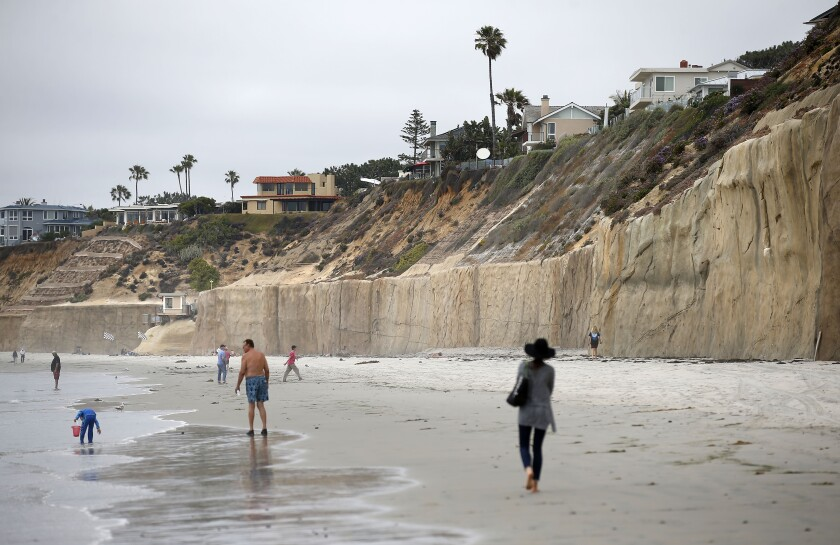 Visitors walks along the coast in Solana Beach, which has a mix of seawalls and natural bluffs. A study by the Center for Climate Integrity concluded that the costs of protecting the coastline against sea level rise would be $400 billion nationwide, and nearly a $1 billion for San Diego alone.