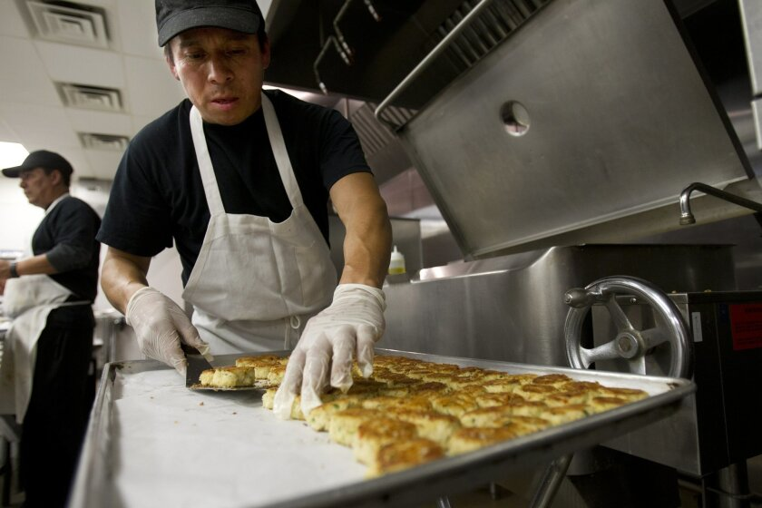 In the kitchen at Behind the Scenes Catering, Giovanni Lopez sears dozens of crab cakes for a dinner event.