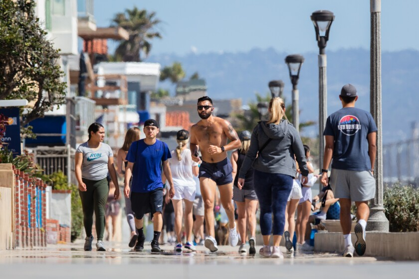 A runner navigates the Strand in Manhattan Beach on Friday. Despite urgings from medical experts and public officials, some walkers and runners disdain face coverings.