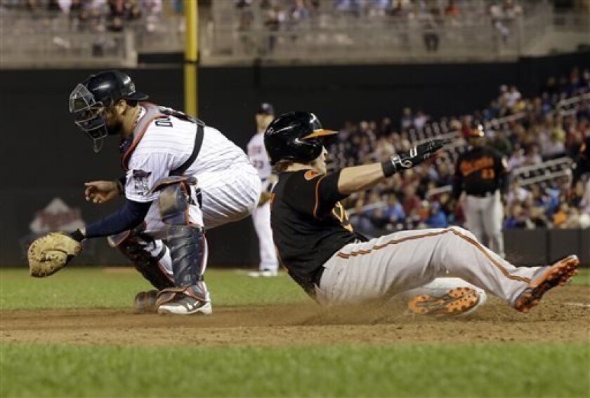 CORRECTS RUNNER NATE MCLOUTH-Baltimore Orioles' Nate McLouth slides in to beat the tag by Minnesota Twins catcher Ryan Doumit to score on a single by Chris Jones in the 10th inning of a baseball game Friday, May 10, 2013 in Minneapolis. The Orioles beat the Twins 9-6. (AP Photo/Jim Mone)