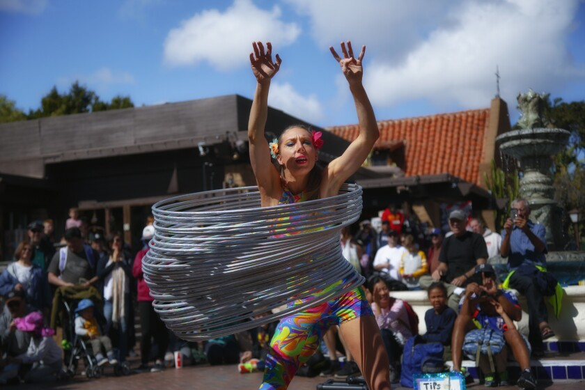 Hillary Matson from Canyon Lake uses 30 hula-hoops to create her giant slinky during a her performance for the crowd attending Seaport Village's Spring Busker Festival in 2017.