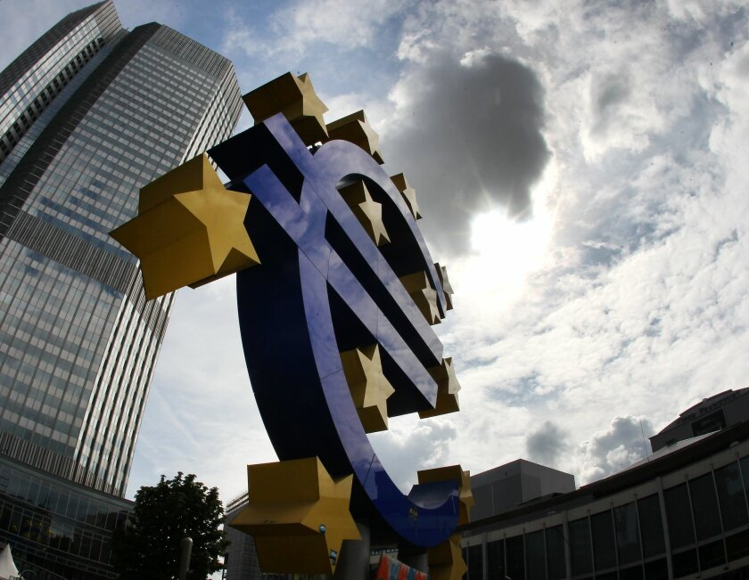 FILE - In this July 31, 2012 file photo the euro sculpture stands in front of the headquarters of the European Central Bank, ECB, in Frankfurt, Germany. The crisis in Ukraine and a hesitant recovery in Europe are casting shadows over the European Central Bank's meeting Thursday, Aug. 7, 2014. Economists say the monetary authority for the 18 countries that use the euro will look to reassure markets that it is ready to add more stimulus measures if the economy takes a serious turn for the worse. (AP Photo/Michael Probst, File)