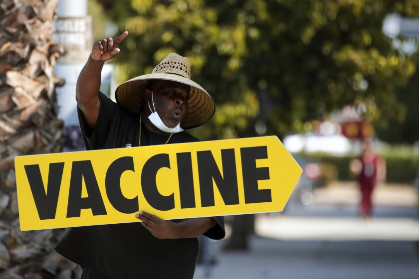 Willie Golden directs people toward a mobile COVID-19 vaccine clinic in Los Angeles on July 16.