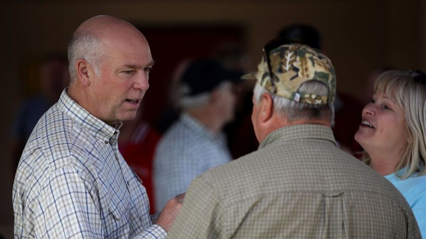 Republican congressional candidate Greg Gianforte, left, talks with supporters during a campaign mee