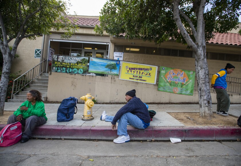 Tyrone Dixon, 53, center, waits with fellow homeless people outside the Echo Park Community Center.