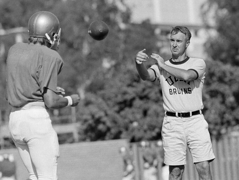 UCLA football coach Pepper Rodgers, right, tosses a ball to quarterback Mark Harmon during a team practice session on Sept. 13, 1972.