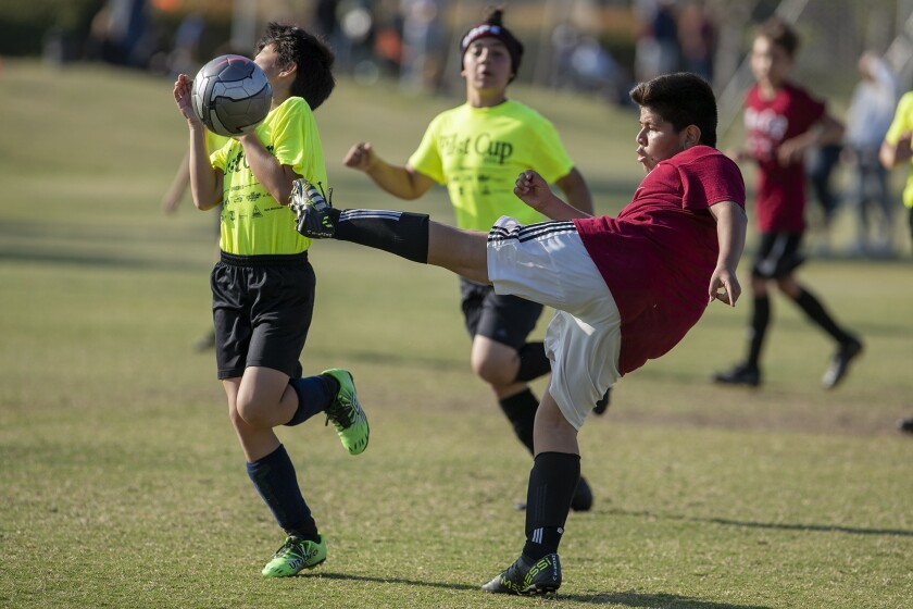 Costa Mesa Pomona's Jorgely Mendez, right, kicks a ball into Newport Coast's Jordan Lum in a boys? f