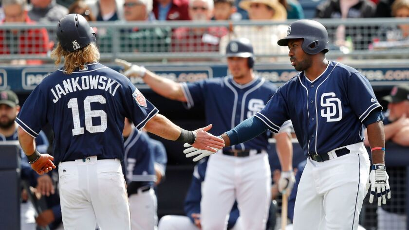 Travis Jankowski is greeted by Jose Pirela, right, after scoring a run during a spring training game. Hunter Renfroe looks on.