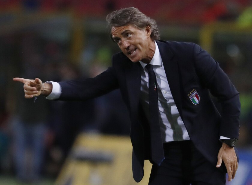 """FILE - In this Friday, Sept. 7, 2018 file photo, Italy coach Roberto Mancini gestures during the UEFA Nations League soccer match between Italy and Poland at Dall'Ara stadium in Bologna, Italy. Italy coach Roberto Mancini has tested positive for the coronavirus days before the international break. The Italian soccer federation says that Mancini is """"completely asymptomatic"""" and is self-isolating at his house in Rome. The Italy squad will meet up on Sunday. It plays an international friendly against Estonia on Wednesday and hosts Poland in the Nations League four days later. (AP Photo/Antonio Calanni, File)"""