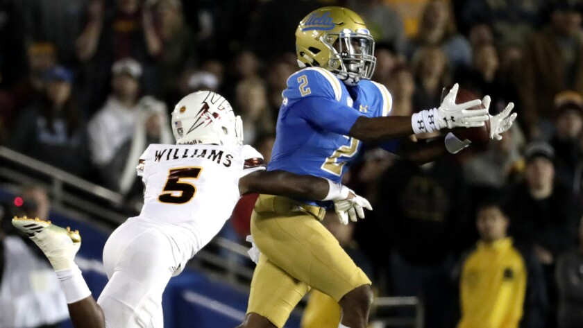 UCLA receiver Jordan Lasley hauls in a long pass from Josh Rosen against Arizona State defensive back Kobe Williams during the second quarter.