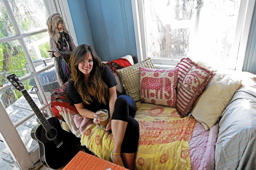 """Airbnb touts """"home sharing"""" in its ads and political campaigns, but nearly two-thirds of its listings in L.A. and other big markets are for whole units. Above, Hope Arnold is shown in 2013 on the couch she slept in when renting out her bedroom in Silver Lake."""