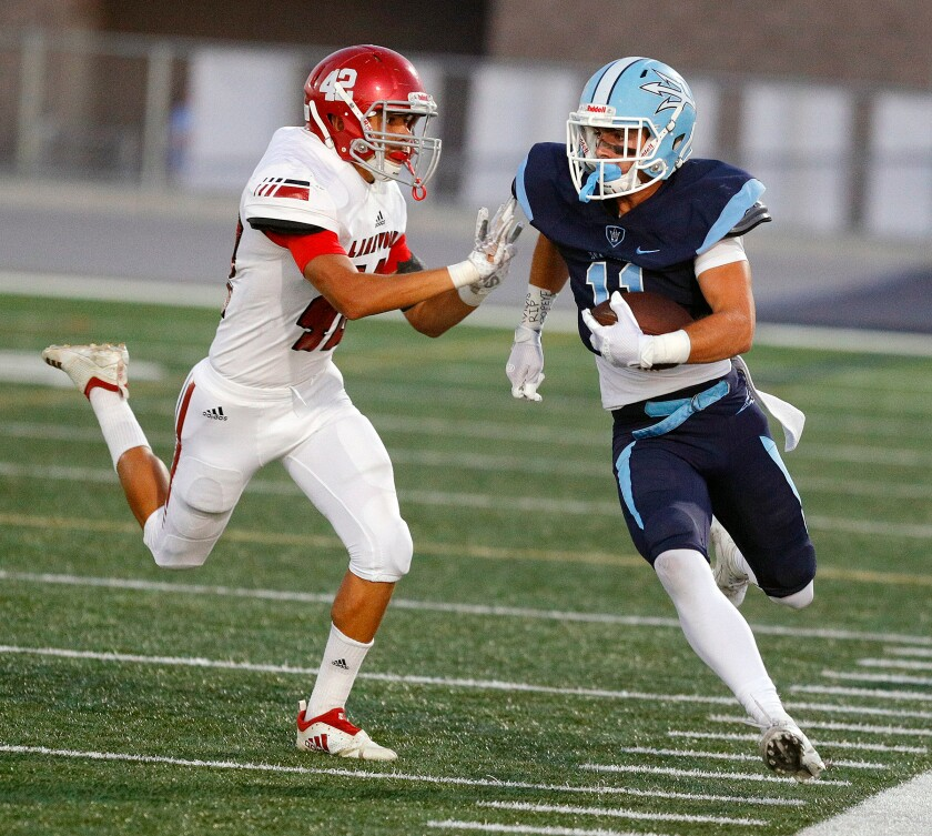 Corona del Mar's Bradley Schlom, pictured running for a first down while Lakewood's Travis Perryman tries to push him out of bounds on Sept. 13, has 11 receiving touchdowns this year.