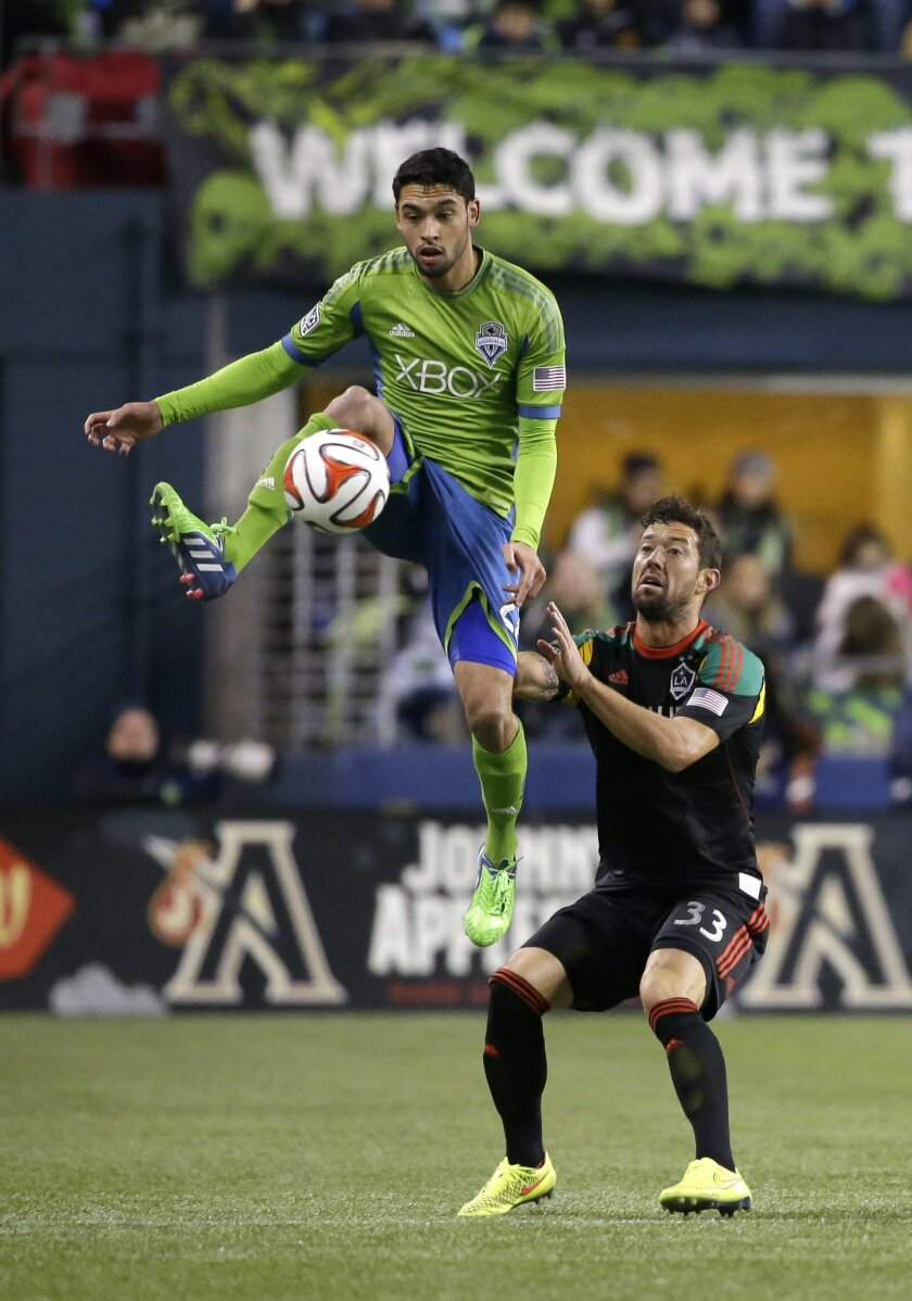 Seattle Sounders midfielder Lamar Neagle, left, leaps above Los Angeles Galaxy defender Dan Gargan, right, to kick the ball in the first half of the second leg of the MLS western conference final soccer match, Sunday, Nov. 30, 2014, in Seattle. (AP Photo/Ted S. Warren)