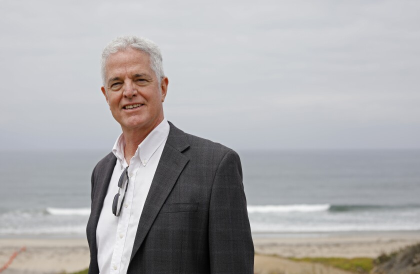 Author John Fanestil is photographed against the Pacific Ocean, wearing a black jacket and white button-down shirt.