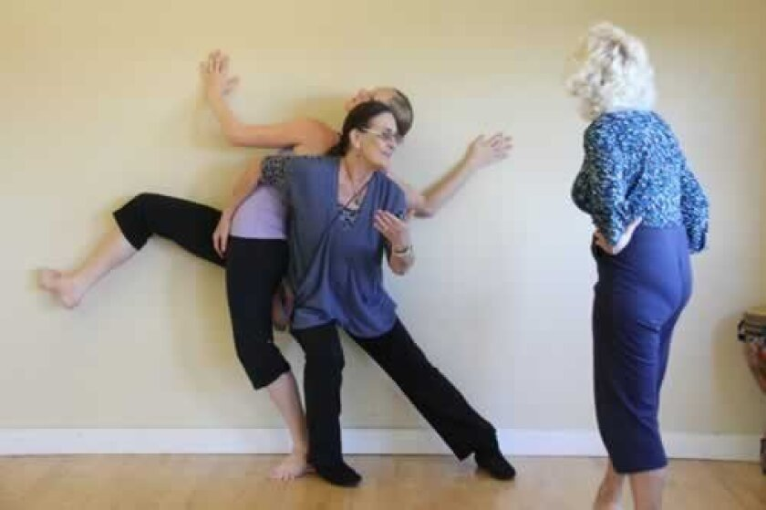 """In Rehearsal: Jean Isaacs works out a move with Blythe Barton, preparing for the world premiere of """"The Door is Open: An Intergenerational Dance Project,"""" which features 12 dancers, ages 60-84, sharing the stage with nine young pros. (With her back to camera is Marysa Andriola). Photo Kira Corser"""