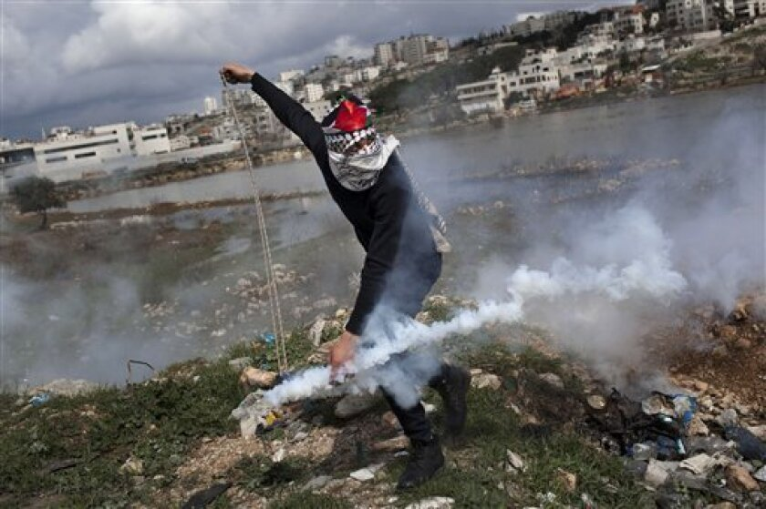 A masked Palestinian throws back a gas canister previously shoot by Israeli forces, not pictured, during a protest to support Palestinian prisoners, outside Ofer, an Israeli military prison near the West Bank city of Ramallah, Tuesday, Feb. 19, 2013. Palestinian protesters clashed with Israeli sold