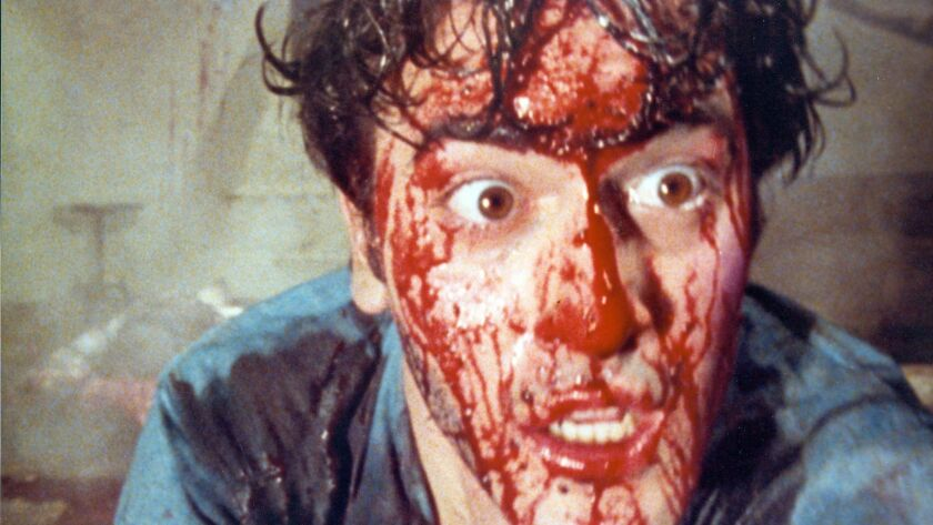 "Bruce Campbell covered in fake blood in the 1981 movie ""The Evil Dead."""