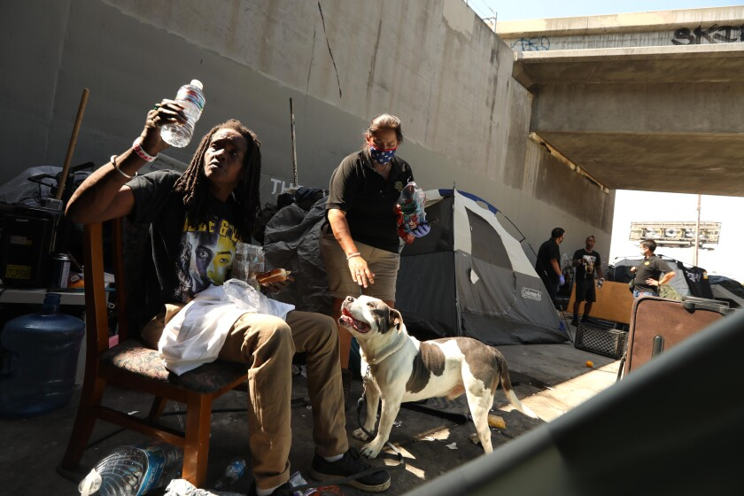 Los Angeles Homeless Services Authority outreach worker Monica Palma, center, visits with Kim M. and her dog in July.