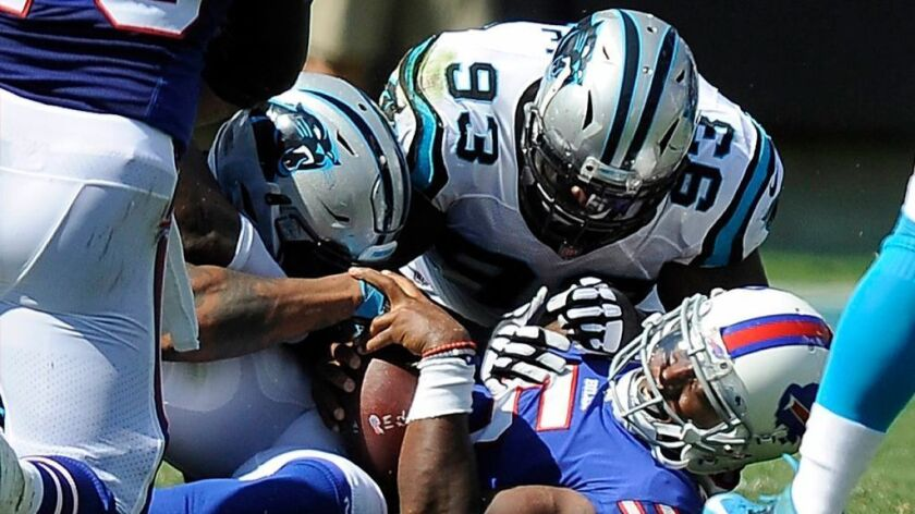 Carolina Panthers defensive ends Julius Peppers, left, and Kyle Love sack Tyrod Taylor of the Buffal