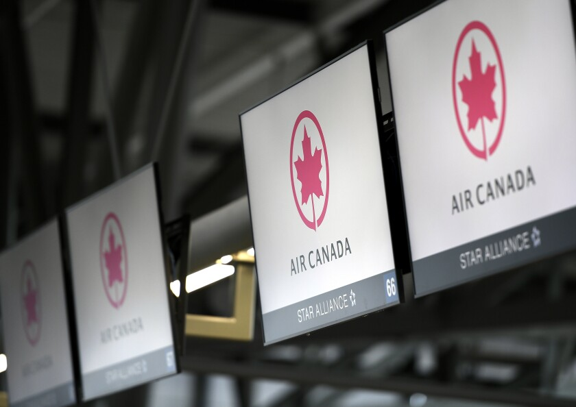 FILE - This May 16, 2020 file photo shows Air Canada check screens at Ottawa International Airport in Ottawa, Ontario, Canada. The U.S. government is seeking to fine Air Canada more than $25 million over what it says have been slow refunds for passengers whose flights were canceled since the pandemic started. The Transportation Department said Tuesday, June 15, 2021, it has received more than 6,000 consumer complaints about Air Canada since March of last year. (Justin Tang/The Canadian Press via AP)