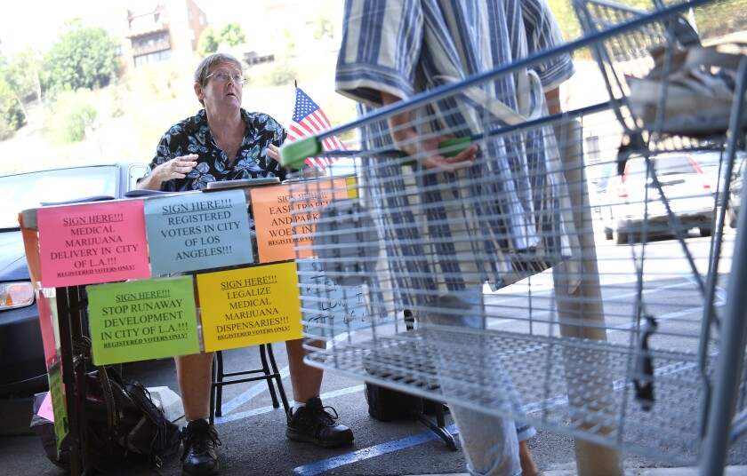 Tim Ecker collects signatures from grocery store patrons in Silver Lake on Tuesday.