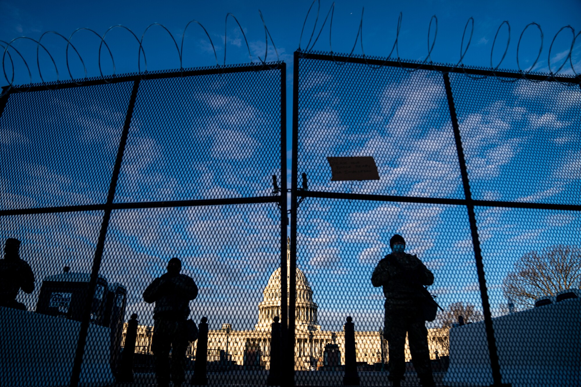 ational Guard troops stand behind security fencing with the dome of the U.S. Capitol Building behind them.