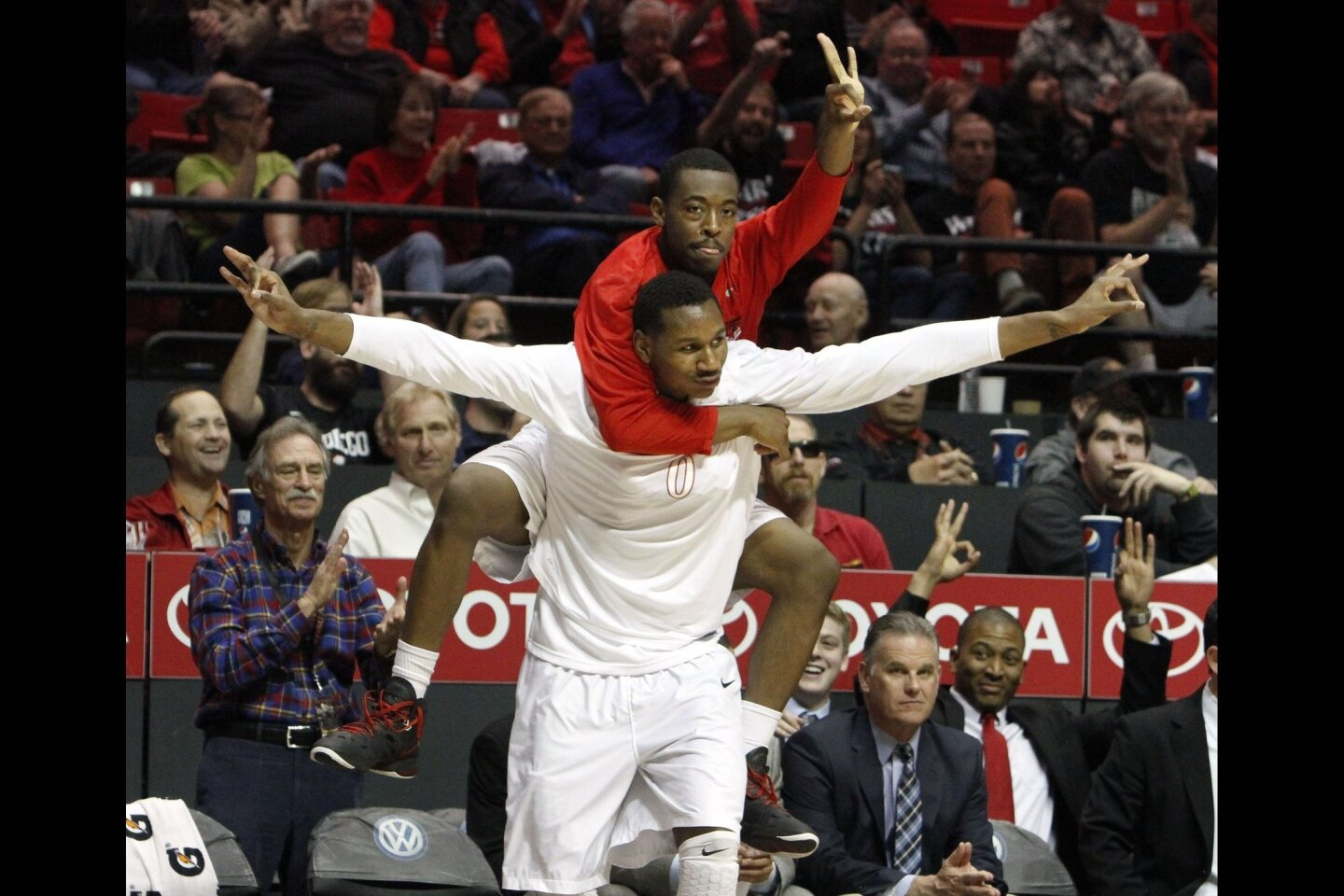 The Aztecs' Xavier Thames jumps on the back of Skylar Spencer as they cheer on their teammates during the second half against St. Katherine College at the Viejas Arena in San Diego on Friday, December, 27, 2013.