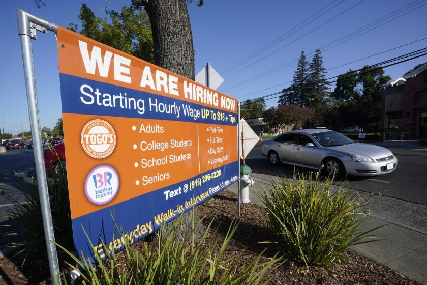 Un auto pasa frente a un letrero de contratación de Sacramento, California